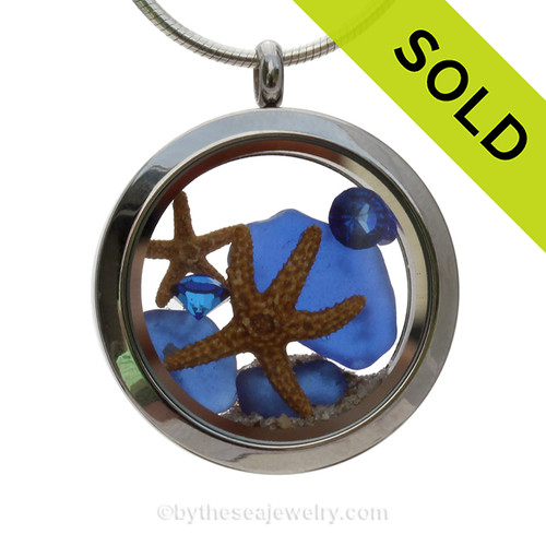 Cobalt Blue Sea Glass in a crystal and stainless steel locket combined with a two baby starfish and vivid blue Crystal Gems. Finished with real beach sand for your personal beach on the go! SOLD - Sorry this Sea Glass Locket is NO LONGER AVAILABLE!