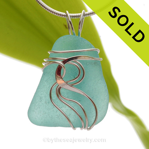 A BEAUTIFUL Bright Aqua Blue Sea Glass Pendant set in our Signature Waves© setting in Sterling Silver. This perfect natural beach found sea glass in our WAVES sterling necklace pendant setting that maximizes the bling of silver yet leaves most of the sea glass open and UNALTERED from the way it was collected on the beach.