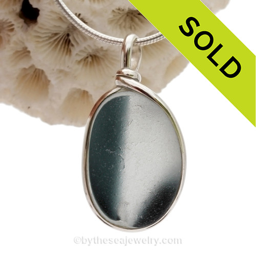 A vivid mix of Smoked Teal in a base of pure white endoday sea glass from England set in our Original Wire Bezel© necklace pendant setting.