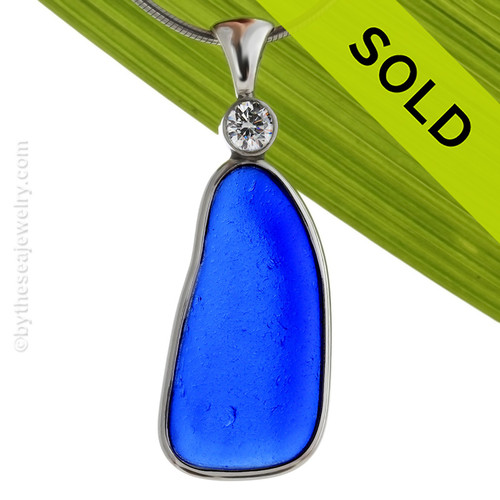 "A HUGE Genuine Sea Glass Pendant in a vivid Cobalt Blue in our Deluxe Wire Bezel and set with A Brilliant Premium ""Diamond"" or CZ. Our Deluxe Wire design that leaves the glass UNALTERED from the way it was found on the beach.  Added Brilliance - Incorporates a brilliant cut 6MM Premium CZ in a bezeled tube setting."
