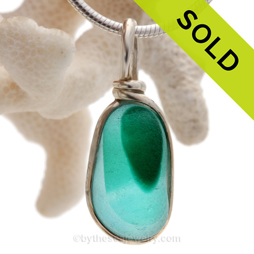 This Rare Seaham sea glass multi Teal and Light blue necklace pendant is set in our Deluxe Wire Bezel© pendant setting.