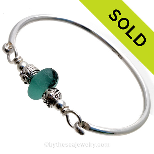 A beautiful Stunning and Thick and Round Deep Mixed Aqua Green sea glass combined Sterling Silver Fish Beads on a Solid Sterling Premium Round Bangle Bracelet. This is a small to Medium bangle at 7 inches but can be sized down upon request. Simply put size needed in comments section and we will resize and ship the same day