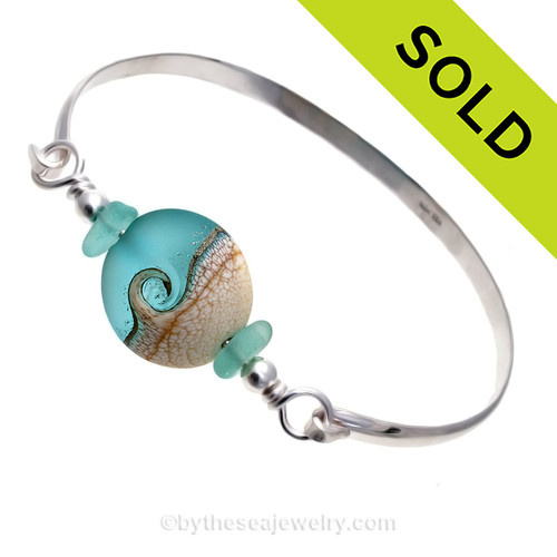 Genuine Aqua Blue Sea Glass Bangle Bracelet set with a handmade lamp work glass wave bead in blue with sterling end beads on a solid sterling half round premium bangle bracelet.