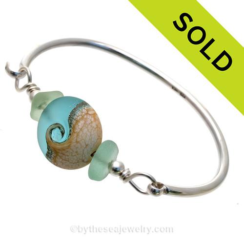 Seafoam Green Genuine Sea Glass Bangle Bracelet set with a handmade lampwork glass Wave bead set with Sterling Details on a Solid Sterling Round Bangle Bracelet.