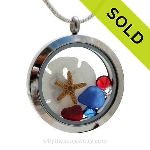 Cobalt Blue and a small piece of Ruby Red Sea Glass in a crystal and stainless steel locket combined with a baby starfish, sandollar and crystal gems.