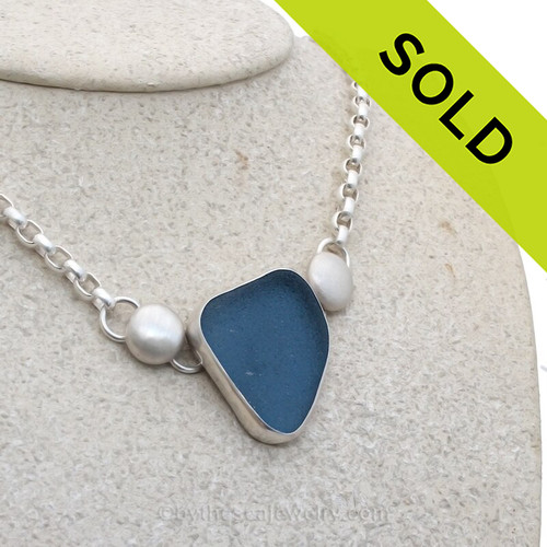 A stunning deep cornflower blue sea glass set in fine silver with sterling details on a oval rolo chain.