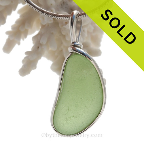 A Cool bean shaped Piece of Yellowy Seawater Green beach found glass set in our Original Wire Bezel© pendant setting.