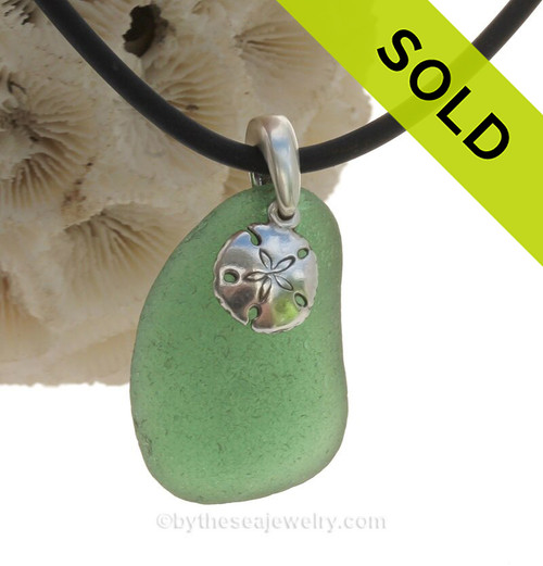 A nice piece of Green  Natural Sea Glass Necklace Set On Silver Bail With Black Neoprene Cord with sterling clasps and finished with a solid sterling Sandollar Charm.