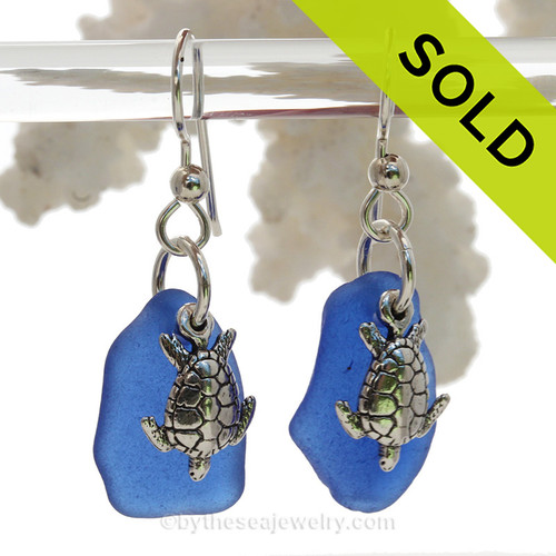 A pair of Natural Surf Tumbled rich Cobalt Blue Sea Glass Earrings with Solid Sterling Sea Turtle Charms.