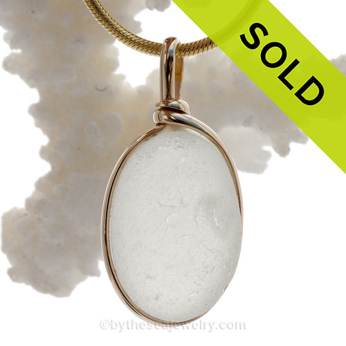 A lovely thick naturally aged pure white with large internal air bubble in a natural sea glass piece set in our Original Wire Bezel setting in 14K Rolled Gold setting.