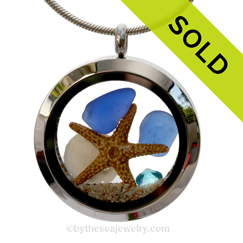Beautiful blue sea glass combined in a stainless steel locket necklace a real starfish, baby sandollar and beach sand. A  great choice for any ocean lover!