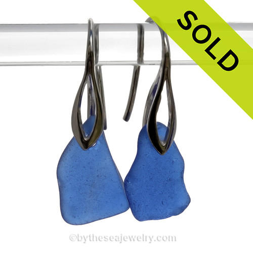 A wee bit larger and Naturally shaped pieces of Vivid Cobalt Blue Sea Glass Earrings on Solid Sterling Silver Deco Hooks Blue sea glass becomes increasing as each wave passes. Shaped only by tide and time and UNALTERED from the way it was found on the beach (other than the hole).