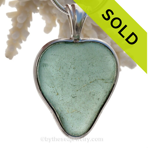 A beautiful Large stunning Aqua Green natural Sea Glass Heart Pendant set in our Deluxe Wire Bezel© setting in mixed Sterling and Gold! This piece stunning flat aqua sea glass and is presented on a professionally our Deluxe Wire Bezel Setting© that leaves the sea glass UNALTERED from the way it was found on the beach.