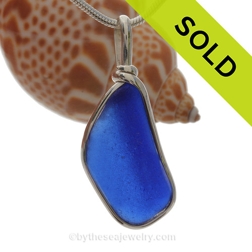 A lovely piece of Cobalt Blue Sea Glass from a bottle or jar bottom set that is set in our Original Deluxe Wire Bezel© necklace pendant in Solid Sterling Silver.   This original By The Sea Jewelry setting that encases the glass in silver and leaves both front and back open so you can feel the texture of this antique top quality glass.