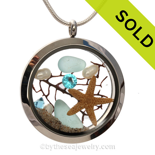 Genuine Aqua Blue combined with a real starfish crystal Aquamarine gemstone , pearls and real beach sand in this screw top stainless steel locket.