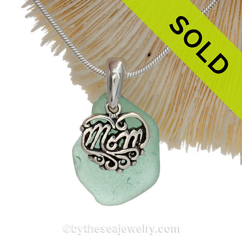 A beautiful petite beach found vivid aqua green sea glass necklace set on a solid sterling cast bail with a sterling silver mom charm.