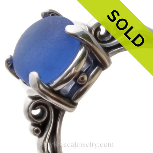 A stunning and lovely piece of PERFECT NATURAL bright Blue beach found sea glass securely set in a solid sterling silver scroll ring.