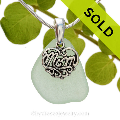 A beautiful petite beach found vivid seafoam green sea glass necklace set on a solid sterling cast bail with a sterling silver mom charm.