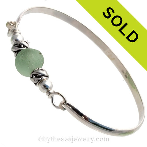 Perfect Sea Green English Sea Glass combined with two Sterling Dolphin Beads on this Solid Sterling Silver Premium Sea Glass Bangle Bracelet.