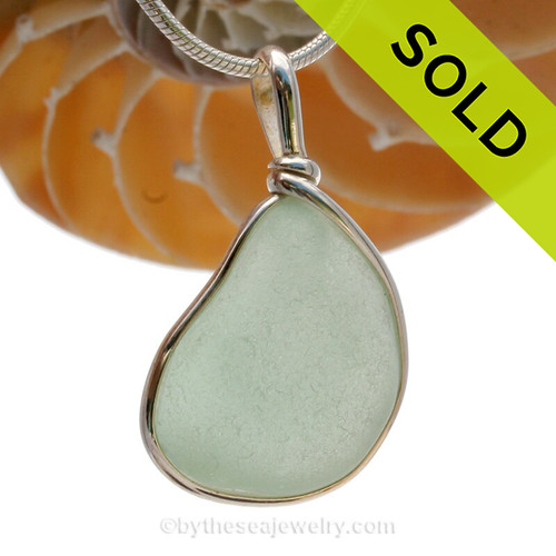 A Lovely Triangle of classic Coke Bottle Green beach found sea glass from is set in our Original Wire Bezel© pendant setting in sterling silver