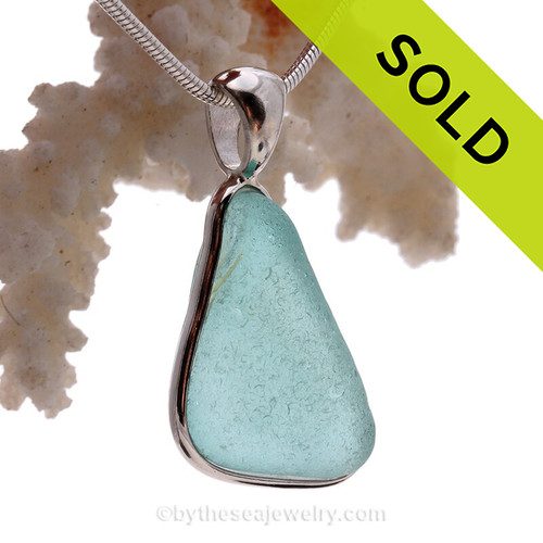 This triangle of  Aqua Genuine Sea Glass set in our Deluxe  Wire Bezel© pendant setting .