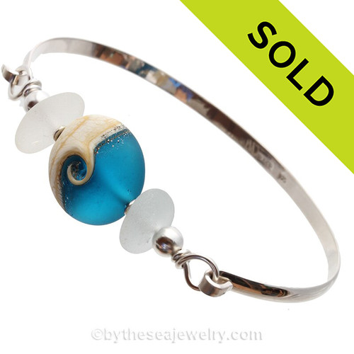 Genuine Pure White sea Glass Bangle Bracelet set with a handmade lamp work glass wave bead in Deep Aqua with sterling end beads on a solid sterling half round premium bangle bracelet.