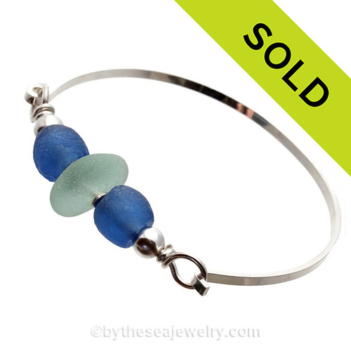 A thick piece of very round piece of sea green English Seaham Sea Glass combined with two bright blue recycled glass beads on a solid sterling bangle bracelet.