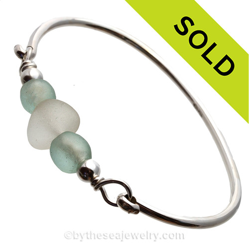 A thick pure white sea glass center bead and two recycled green glass beads set with sterling details on a solid sterling Premium bangle bracelet.