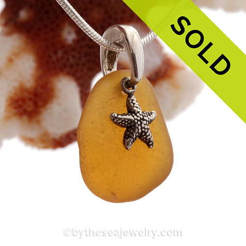 A beautiful beach found vivid amber brown sea glass necklace set on a solid sterling cast bail with a sterling silver starfish charm.