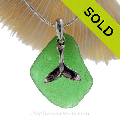 A large piece of Vivid Green sea glass is combined with a solid sterling bail and Large Whale Tail charm in this lovely sea glass necklace.