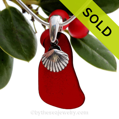 Lovely organic shaped real ruby red sea glass piece set on a solid sterling professionally handcast bail and finished with a sea shell  charm!