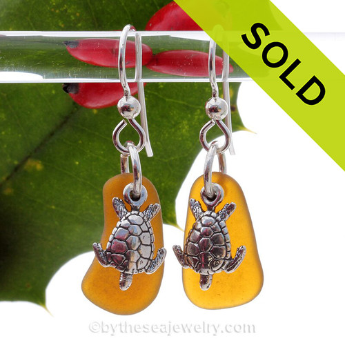 Natural amber brown sea glass pieces are set with solid sterling sea turtle charms and are presented on sterling silver fishook earrings.