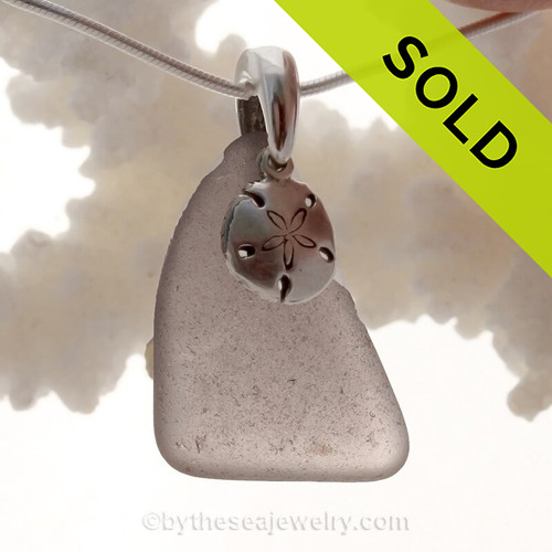 A perfect piece of Deep Purple Certified Genuine Sea Glass in a sterling necklace with a Sandollar charm. Solid Sterling professionally hand cast bail. Stunning Purple Sun Glass from the Island of Betsy Wyeth in Maine.