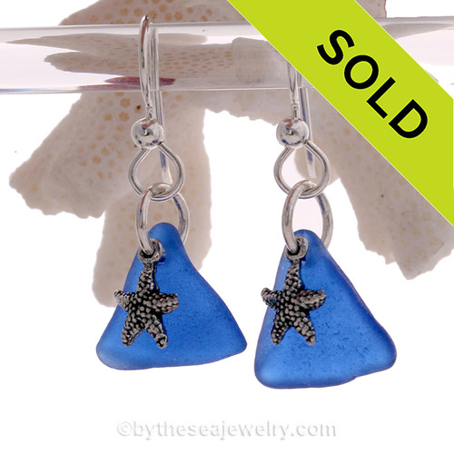 Cobalt Blue sea glass pieces are set with solid sterling  starfish charms and are presented on sterling silver fishook earrings.