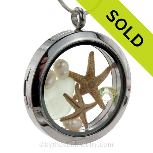 Genuine seafoam green sea glass pieces combined with a two real starfish, pearls a Peridot gem and real beach sand in this stainless steel locket.