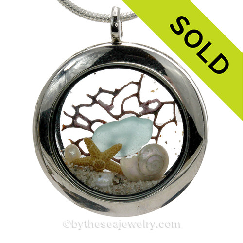 Beautiful piece of aqua genuine sea glass piece combined with a real starfish and pearlized mini nautilus shell. Finished with a real freshwater pearls.