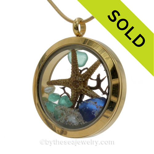 A gold tone stainless steel locket necklace with aqua and blue beach found sea glass pieces and a real starfish and finished with blue crystal gem and real pearls.