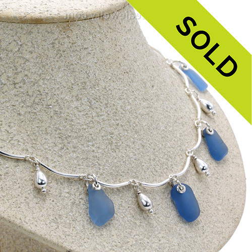 5 pieces of Light Blue Genuine Beach Collected Sea Glass on a Solid Sterling Silver Curved Bar Necklace with Sterling Beautiful Sterling Teardrop Beads in a elegant necklace.