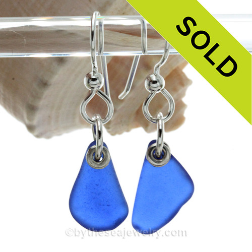 A pair of natural surf tumbled blue sea glass earrings in a lucky cobalt blue on sterling fish hooks. Finished with Solid Sterling Details. Simple and elegant these sea glass earrings are bound to get you compliments!