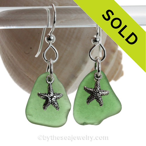 Natural green sea glass earrings are set with solid sterling  starfish charms and are presented on sterling silver fishook earrings.
