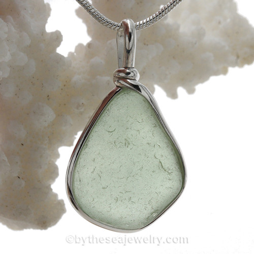 A Lovely fresh Pale Peridot  Green beach found glass from is set in our Original Wire Bezel© pendant setting in sterling silver