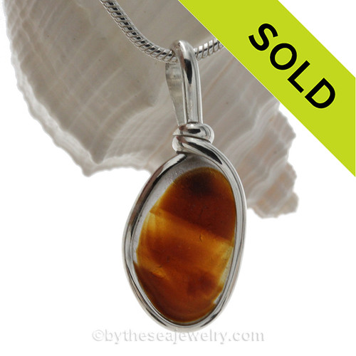 A stunning mix of vivid amber and gold are fused inside this very old English sea glass piece. A great pendant for any necklace.