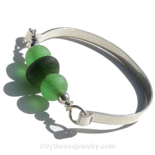 A focal  bead of deep green sea glass piece and bright green recycled glass beads set with sterling details on a thick Solid Sterling flat bangle bracelet.
