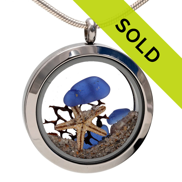 Blue sea glass pieces combined with a real starfish, sea fan, shells and beach sand. Sorry this locket has been sold!