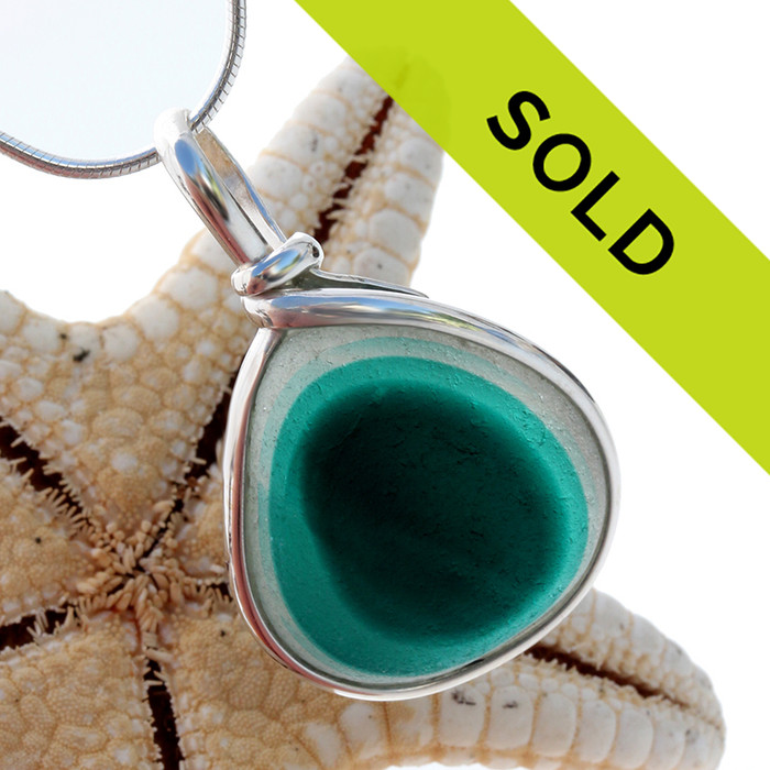 A beautiful mixture of vivid aqua green fused on a pure white sea glass piece. An unusual green that recedes from light to dark. This piece is set in our Original Wire Bezel© setting and leaves this amazing natural sea glass piece UNALTERED from the way it was found on the beach! Sorry this pendant has been sold!