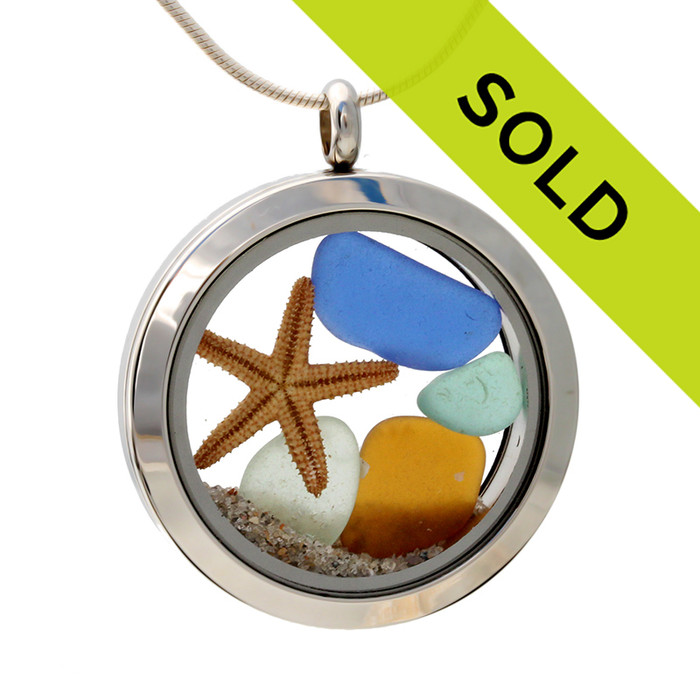 Sea glass in jewel tone colors of green, amber and blues combined with a real starfish and beach sand in this one of a kind stainless steel locket necklace.