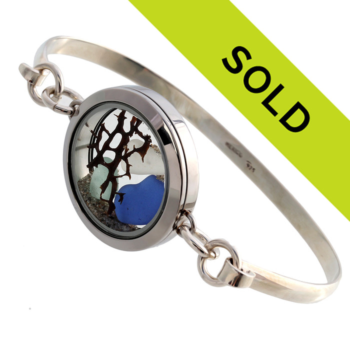Aqua, white and blue sea glass are combined with a vintage sea fan in this stainless steel locket and presented on a solid sterling bangle bracelet.