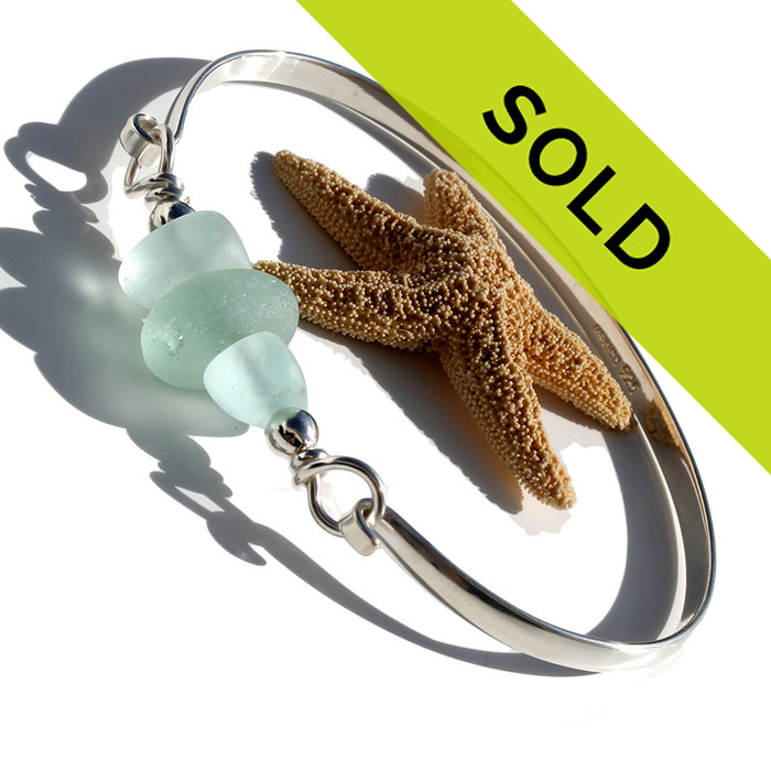 Thick and almost perfectly round seafoam greeb sea glass piece combined with 2 frosted glass beads and  set on our half round solid sterling silver bangle bracelet!