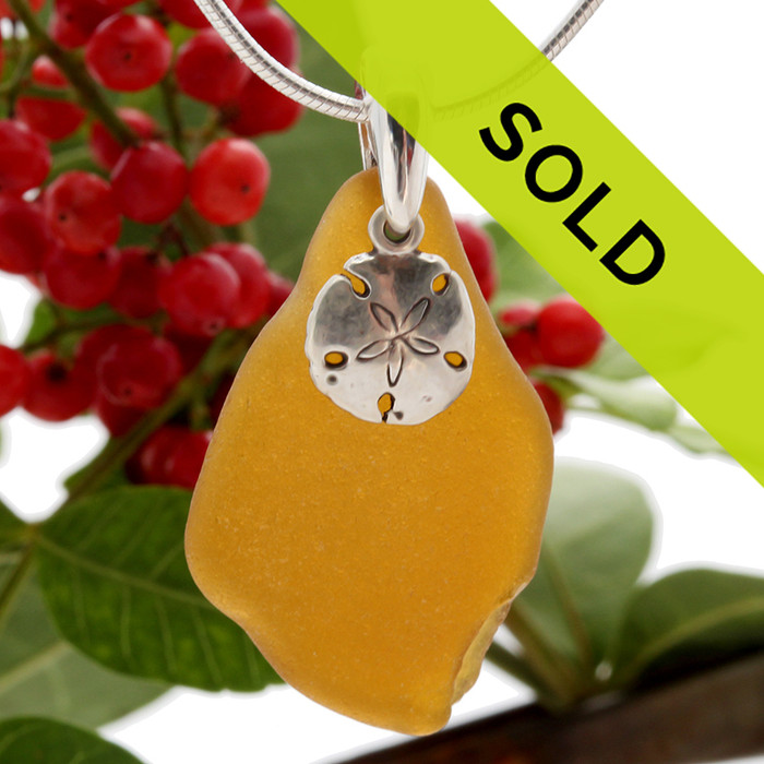A simple but bright vivid amber brown beach found sea glass piece set on a solid sterling professionally hand cast bail and finished with a sterling silver sandollar charm!