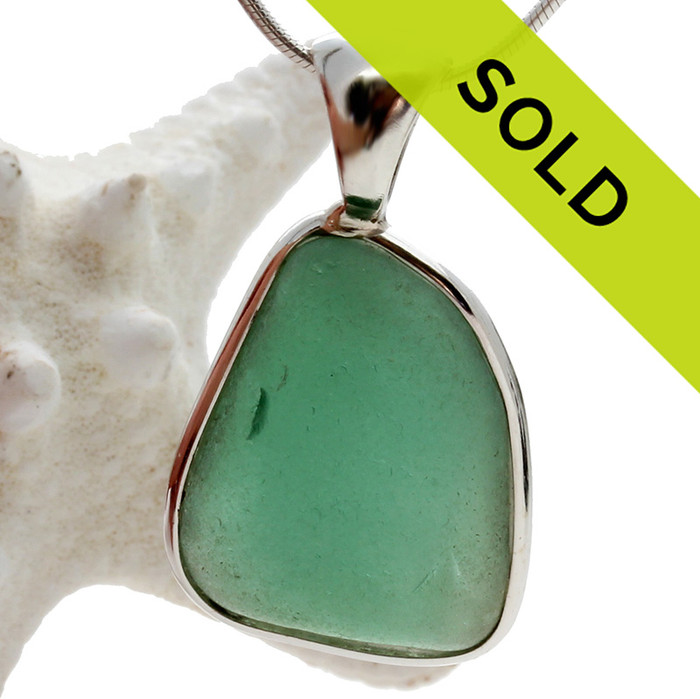A nice older piece of beach found aqua green sea glass set in our Deluxe Wire Bezel neclace pendant setting.